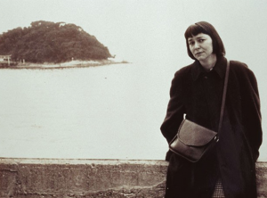Barbara Deming standing in front of a body of water