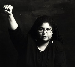 Black and white image of Linda Marie Thurston, with her right fist raised in the air.