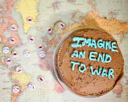 "Chocolate cake with the words ""Imagine and End to War"" piped in blue frosting."